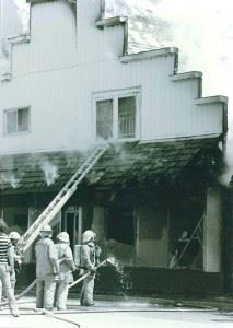 A group of firefighters survey the damage of a building that had caught fire.