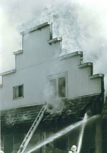 Smoke spills out of an upstairs window, while firefighters put water on it.